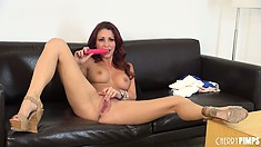 Tattooed redhead works on her pussy using a slick pink dildo