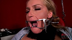 Tied up and with a sex toy opening her mouth, she takes that cock down her throat