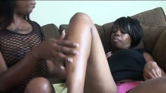 Buxom black lesbians exploring each other's sexual desires on the sofa