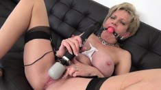Horny mature blonde with big boobs wears a ball gag and brings herself to squirting orgasm