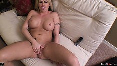 Spreading her body across the couch, the busty blonde fingers her wet pussy to climax